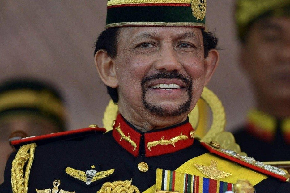 Brunei's Sultan Hassanal Bolkiah smiles as he sits on a stage in Bandar Seri Begawan, in this September 15, 2013 file photo. Oil-rich Brunei will enforce Sharia criminal law next year, the Islamic kingdom's Sultan Hassanal Bolkiah announced on October 22, 2013, with possible punishments including stoning to death for adultery and flogging for drinking alcohol. The law would be enforced from April, said the 67-year-old sovereign, one of the world's wealthiest people who has presided over a shift to more conservative Islam and anti-sedition laws in recent years. REUTERS/Ahim Rani/Files (BRUNEI - Tags: ROYALS CRIME LAW)
